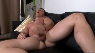 muscle jock strokes his dick and cums on sofa