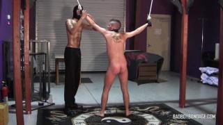 master straps his slave boy onto the bondage frame
