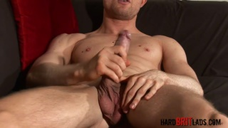 blue-eyed, blond muscle lad strokes his large uncut cock