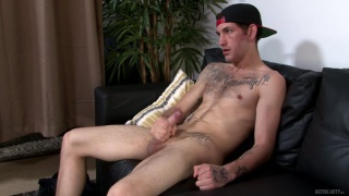 inked guy in baseball cap jerks his cock in first video