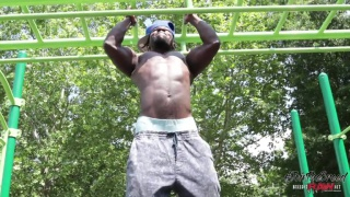 black muscle guy does chin ups in the park