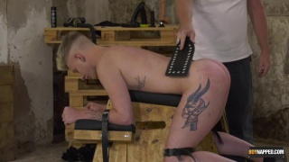 blond lad tied to a spanking bench gets paddled