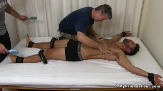 guy strapped to table and tickled by two men