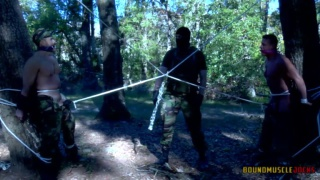 two hunky men tied to trees in the woods