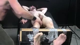 guy restrained in foot stockades and tickled