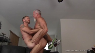 silver daddy holds his boy in the air while fucking him