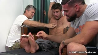 two men tickle a bound guy's under arms and feet