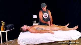 masseur wearing a cap strokes his client's boner on the table