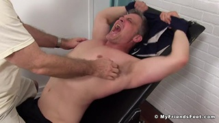 Brenden Cage strapped in the tickling chair