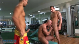 bald hunk sucks off two guys in the gym