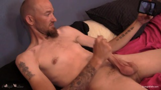 bearded inked man plays with his long cock and big balls