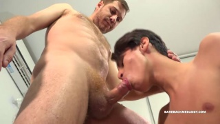 latin twink on his knees sucking beefy daddy's cock