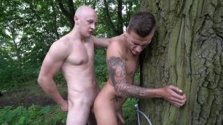 bald top fucks Dom Ully against a tree