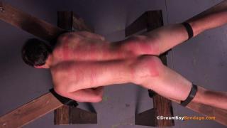 beaten hunk left tied to wooden cross