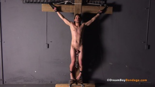 slim lad is bolted to a wooden cross