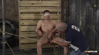 bound guy gets his cock and balls caned