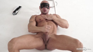 bald masked muscle hunk jerks his dick