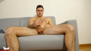 Hunky Tomas Salek sits back on the sofa and strokes