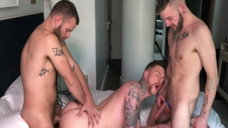 two bearded men share a bottom's mouth and ass