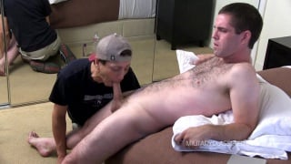 furry ex-army guy sits on edge of bed and gets blowjob
