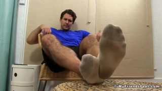 guy plays with his sweaty feet after a workout
