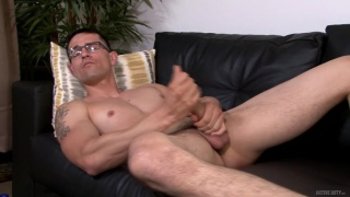 bespectacled guy strokes his cock with both hands