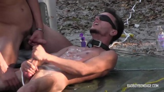blindfolded guy tied to the ground jerks his cock