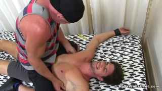 guy tied to the bed and gets his feet tickled
