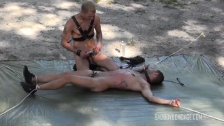 slave boy tied to the ground outside