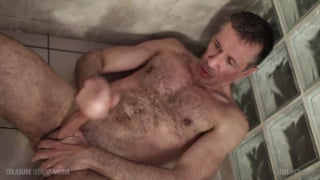 hairy man lies on shower floor jacking off