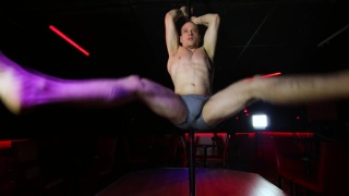 inked guy shows off on the stripper pole