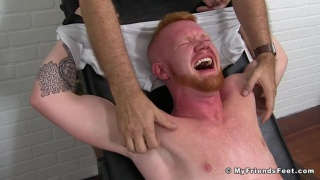 redhead strapped into tickling chair