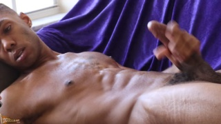 ripped black stud in jockstrap strokes his huge cock