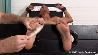 tickling Rico Romero's bare feet with electric toothbrush