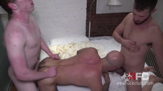 two young guys spit-roast fuck a bald daddy