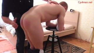 guy bends over stool and prepares for hand spanking