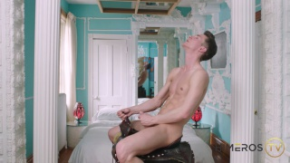 guy sits on a saddle jerking his cock