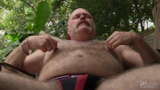 bald beefy bear jerks his pre-cum cock