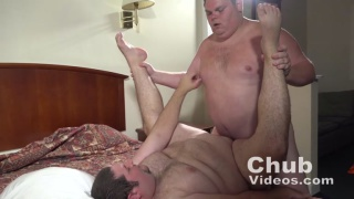 chub holds buddy's ankles and fucks him on the bed