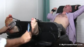 guy's feet tickled with hair brushes