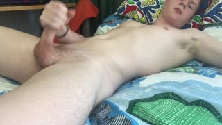 18-year-old smooth guy strokes his long cock in bed